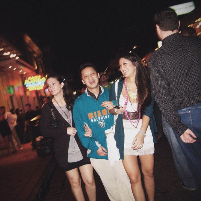 dolphins fan with two young ladies in short dresses on each arm on bourbon street